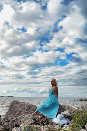 woman sitting in a dress on the bank photo