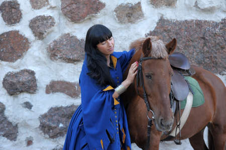 scandinavian girl: beautiful brunette in medieval clothes next to the horse