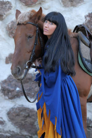 beautiful brunette in medieval clothes next to the horse Stock Photo - 14283848