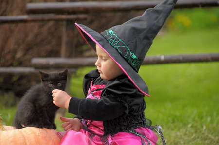 little witch with a black kitten Stock Photo - 10813540