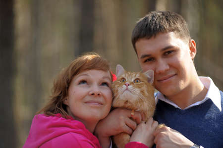 Young couple spends time playing with their pet cat Stock Photo - 12009336