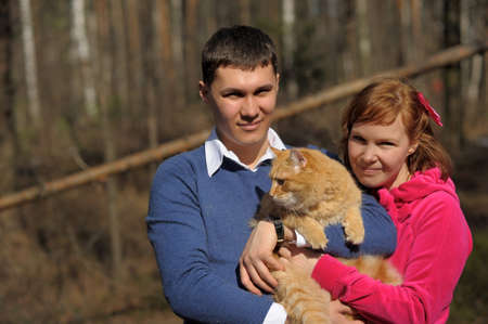 Young couple spends time playing with their pet cat  Stock Photo - 12009338
