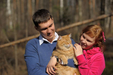 Young couple spends time playing with their pet cat Stock Photo - 12009332