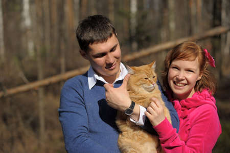 Young couple spends time playing with their pet cat  Stock Photo - 12009340