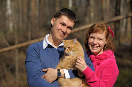 Young couple spends time playing with their pet cat Stock Photo - 12009344