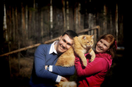 Young couple spends time playing with their pet cat Stock Photo - 12009328