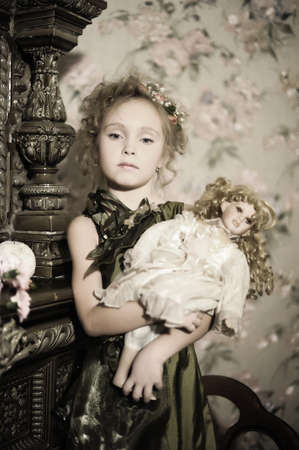 little girl with a doll in hands    photo
