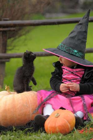 truc: kleine heks met een zwart katje Stockfoto