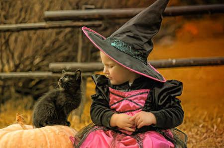 kleine Hexe mit einem schwarzen Kätzchen