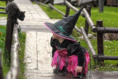 little witch with a black kitten Stock Photo - 10886304