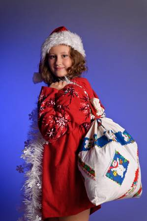 Girl teenager in santa hat with Christmas gifts photo