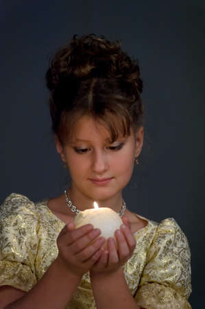 Young beautiful, girl portrait by glow of candlelight photo