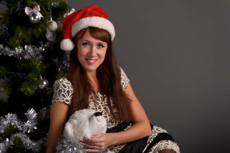 The young woman with a Christmas cap at a fur-tree Stock Photo - 11038163