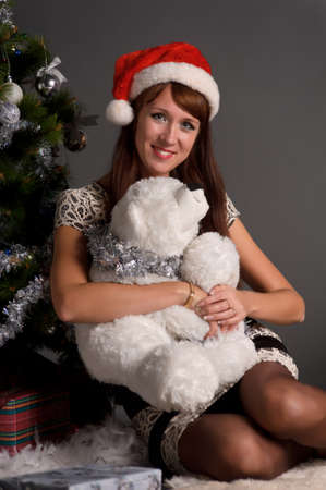 The young woman with a Christmas cap at a fur-tree Stock Photo - 11038162