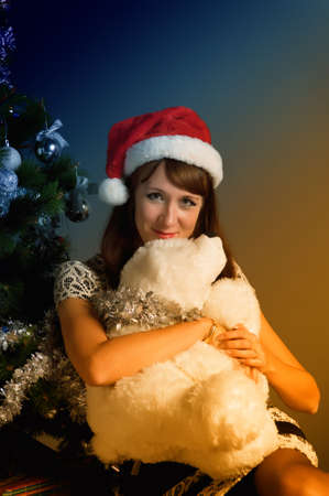 The young woman with a Christmas cap at a fur-tree Stock Photo - 11038160
