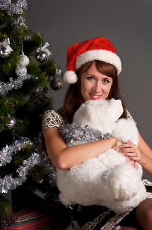 The young woman with a Christmas cap at a fur-tree photo