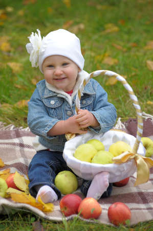 The little girl with a basket of apples  Stock Photo - 11037137