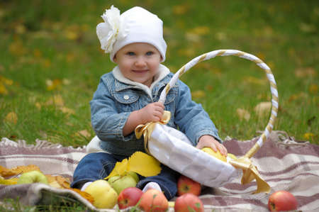 The little girl with a basket of apples Stock Photo - 11037132