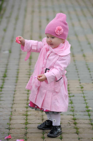 waterproof cape: The little girl in a pink raincoat and a hat  Stock Photo