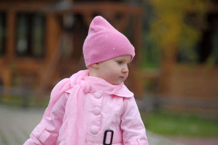 The little girl in a pink raincoat and a hat  photo