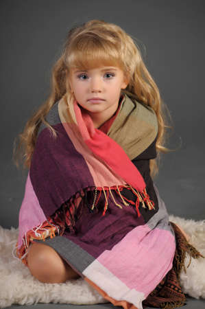 The little girl muffled in a scarf to be warmed  photo