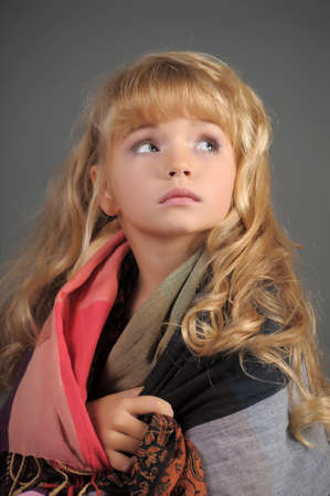 The little girl muffled in a scarf to be warmed  Stock Photo