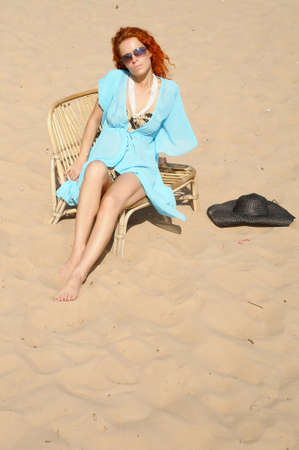 young woman sitting on the beach photo