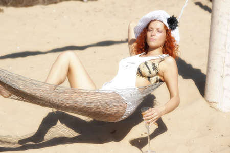 girl lying on the beach in a hammock photo