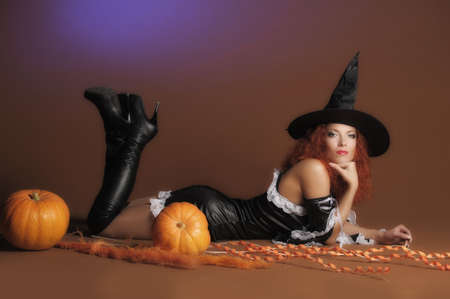 Beautiful red-haired witch with a pumpkin  Stock Photo - 11190255