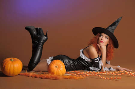 Beautiful red-haired witch with a pumpkin Stock Photo - 11190280