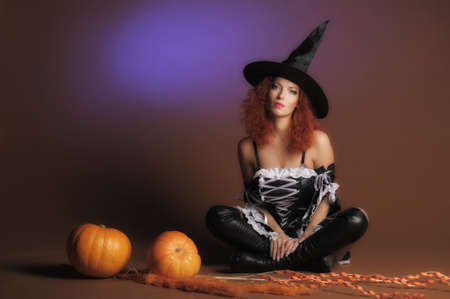 Beautiful red-haired witch with a pumpkin  Stock Photo - 11190256