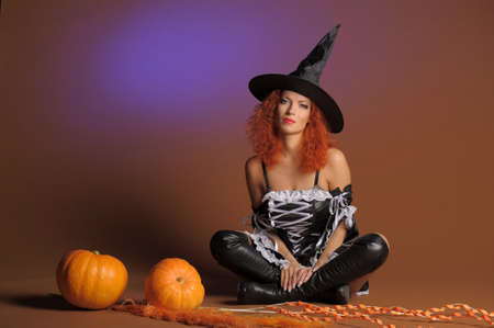 Beautiful red-haired witch with a pumpkin Stock Photo - 11190260