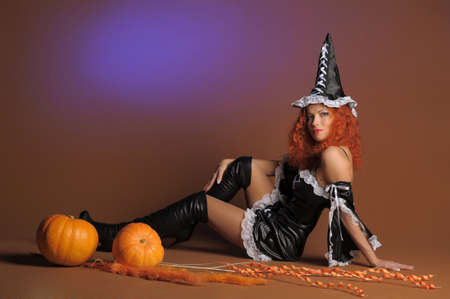 red haired woman: Beautiful red-haired witch with a pumpkin