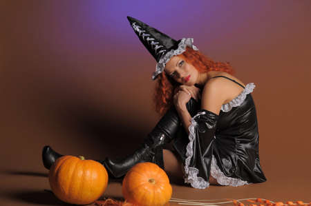 Beautiful red-haired witch with a pumpkin