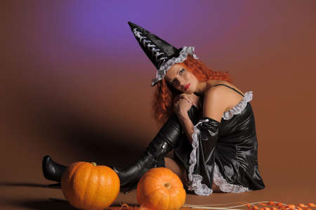 Beautiful red-haired witch with a pumpkin Stock Photo - 11190278