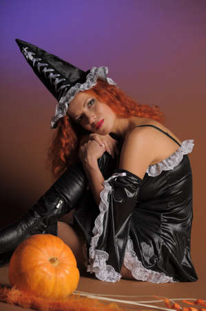 Beautiful red-haired witch with a pumpkin Stock Photo - 11190286