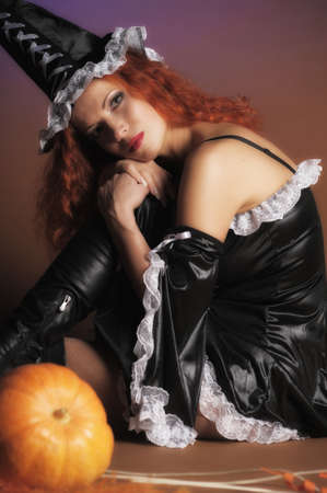Beautiful red-haired witch with a pumpkin  photo