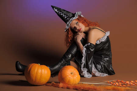 girl lying studio: Beautiful red-haired witch with a pumpkin