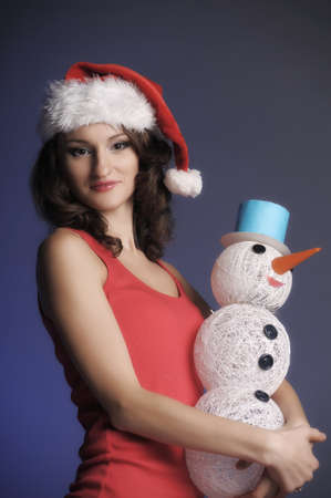 girl in a Christmas hat with snowman photo
