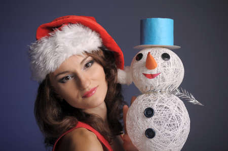 girl in a Christmas hat with snowman Stock Photo - 11423026