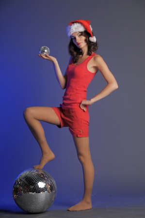 Santa-rina with her feet on a disco ball and holding a smaller on in her hand photo