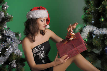 young woman in a santa hat and a gift for Christmas trees photo