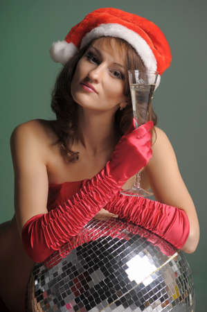 young woman in a santa hat and a glass of champagne photo