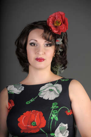 a beautiful young woman with poppies on a dress and in the hands photo