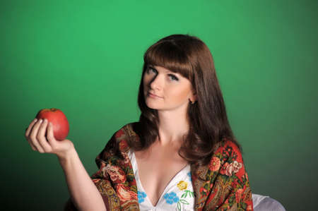 The young beautiful woman in Russian scarf with apples in hands photo