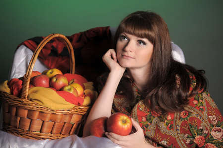 The young beautiful woman in Russian scarf with apples photo