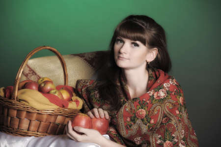 The young beautiful woman in Russian scarf with apples Stock Photo - 11961291