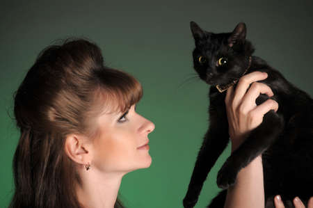 Young woman with a black cat looking at each other  photo