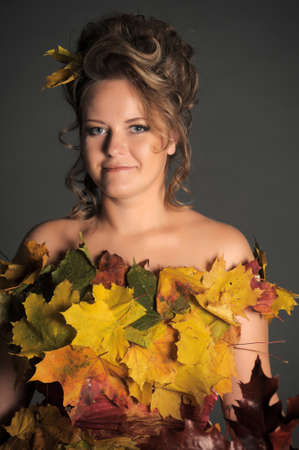 woman with a dress made of autumn leaves photo