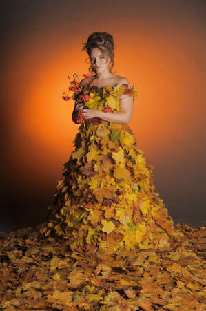 woman with a dress made of autumn leaves